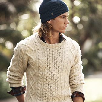 Man in cable cream sweater & knit cap