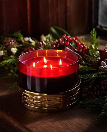 Lit four-wick red candle in gold-trim holder