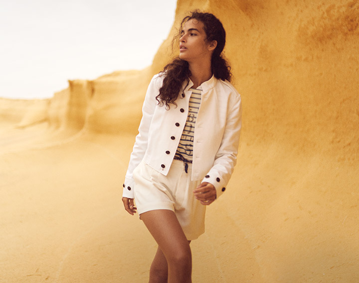 Woman in white jacket, striped tee & drawstring white shorts
