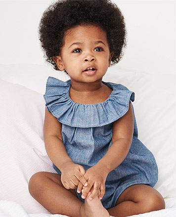 Baby girl wears chambray one-piece with ruffled collar.
