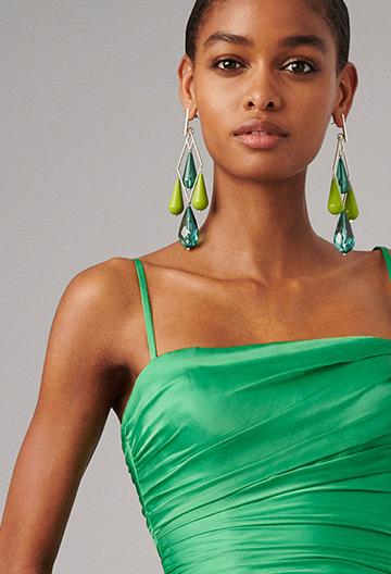 Woman wears oversize blue & green drop chandelier earrings