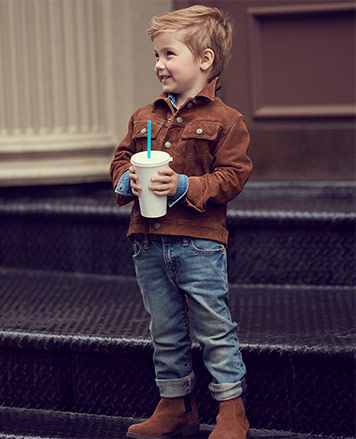 Boy wears jeans with rolled cuffs and brown jacket.