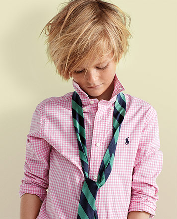 Boy wears pink gingham button-down with green-and-blue tie.
