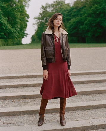 Woman wears red dress under brown leather bomber jacket with brown leather boots.