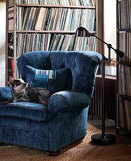 Black swing-arm floor lamp next to blue armchair