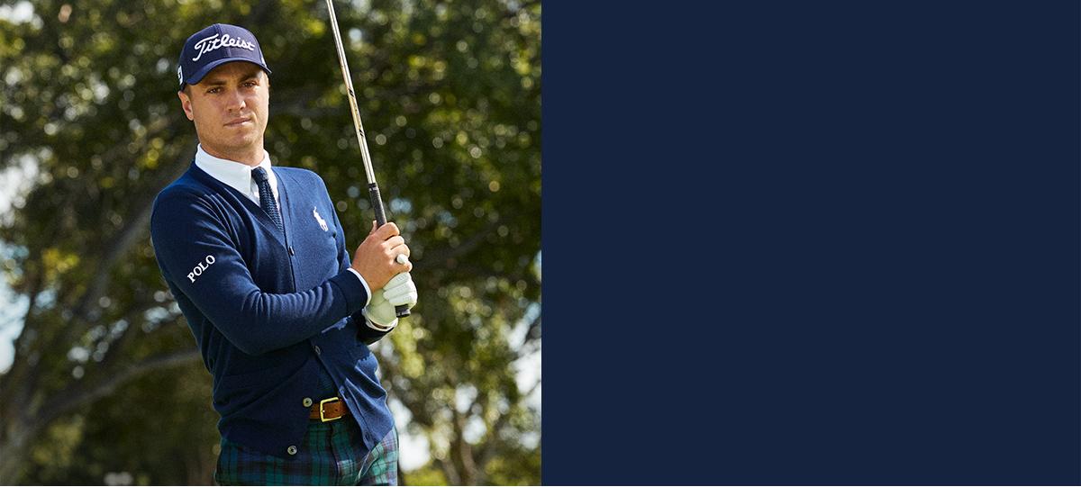 Justin Thomas wears navy cardigan and plaid pants while swinging golf club.