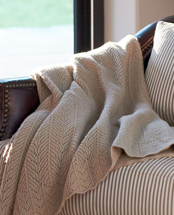 Knit beige throw blanket draped over striped cushioned chair