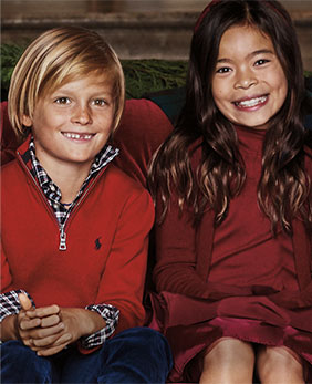 Kids wear festive holiday outfits in shades of red.