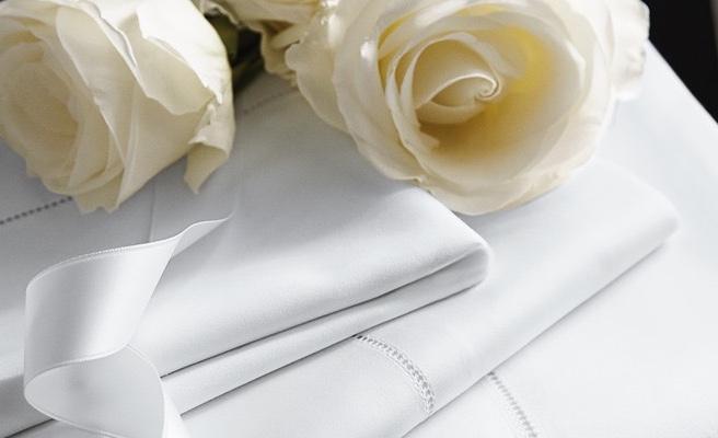 Folded white pillowcases & sheets next to white rose