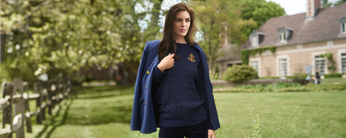 Model in navy cable knit with navy blazer draped over shoulders