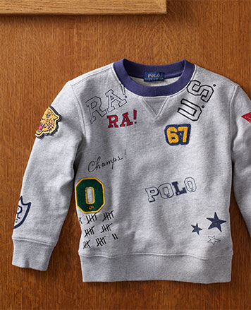 Grey crewneck sweatshirt with doodles and patches.