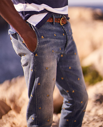 Man on beach in jeans paired with brown leather belt