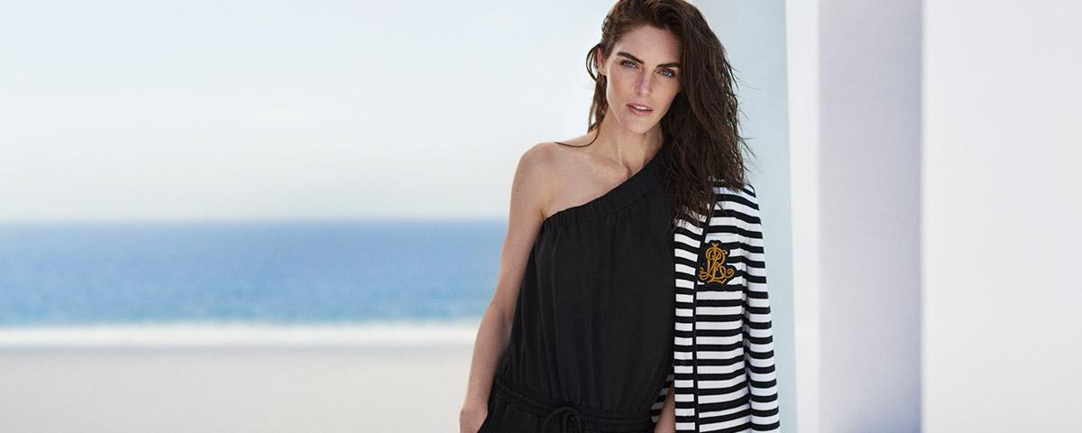 Model in one-shoulder jumpsuit with striped blazer draped over shoulder