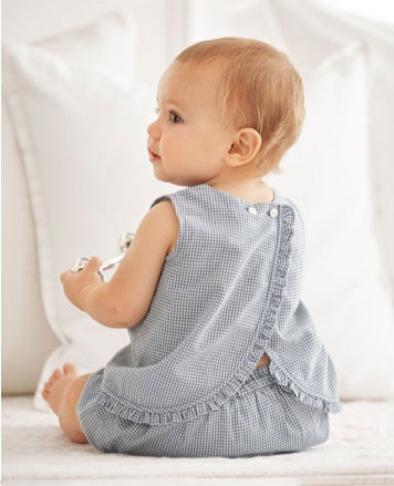 Baby girl wears blue gingham top and shorts.
