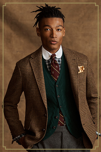 Man in houndstooth tan sport coat layered over green cable cardigan