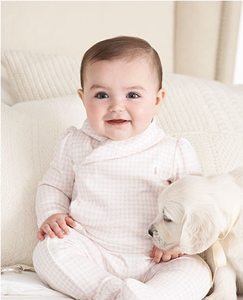 Baby girl wears pink and white checked coverall.