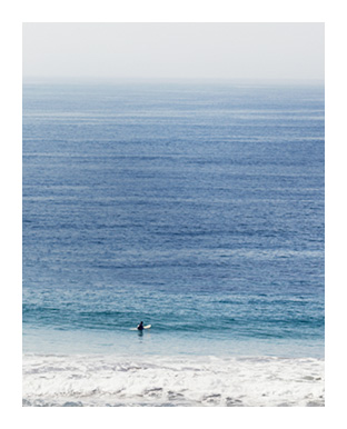Faraway image of surfer in blue ocean on white sand beach