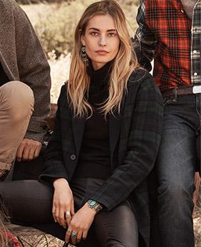 Woman wears dark plaid overcoat with leather leggings.