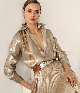 Woman in pleated metallic skirt & shimmering blouse