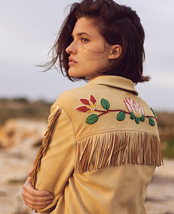 Woman in beaded fringe deerskin coat