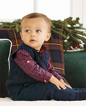 Baby wears navy sweater vest over red flannel shirt and leggings.