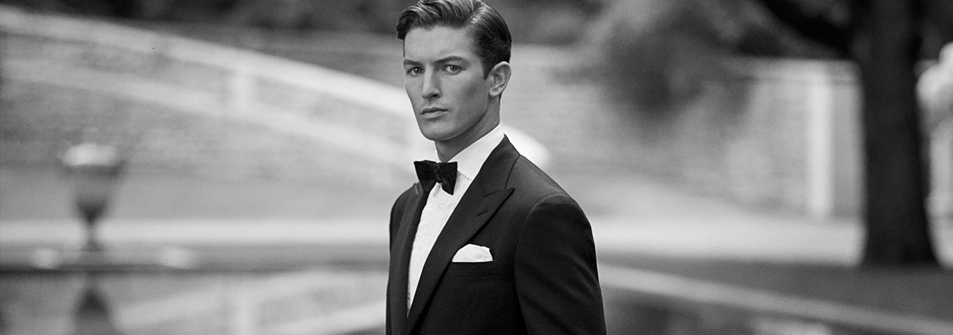 Man facing camera in black tuxedo paired with white pocket square