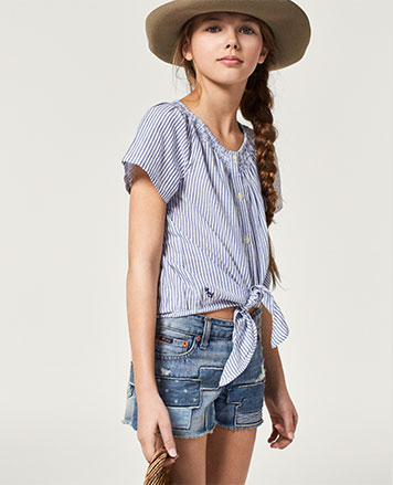Girl wears denim shorts with tie-front shirt and sun hat.