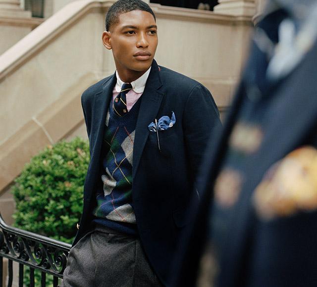 Man wears argyle sweater vest under blazer.