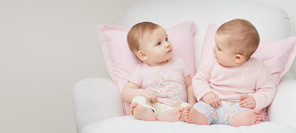 Babies wear light pink and pastel floral outfits.