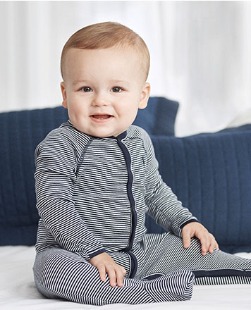 Baby boy wears blue-and-white striped coverall.