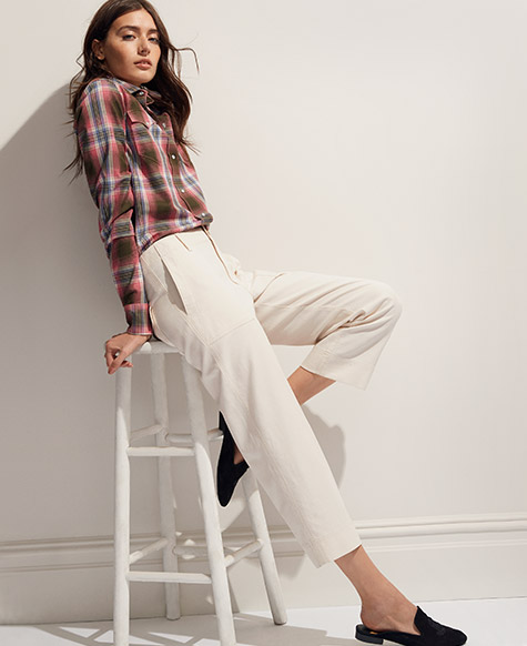 Woman in cropped white pleated pants