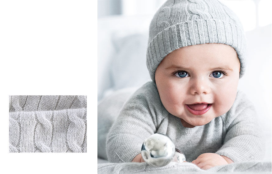 Left: Close-up of cable-knit cashmere. Right: Baby wears grey knit coverall & grey cable-knit hat