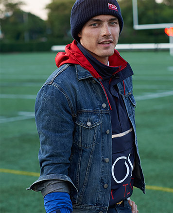 Man in knit hat & denim jacket layered over pullover