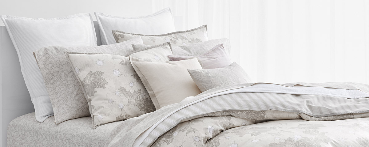 Bed made with grey and white linens with subtle floral patterns.