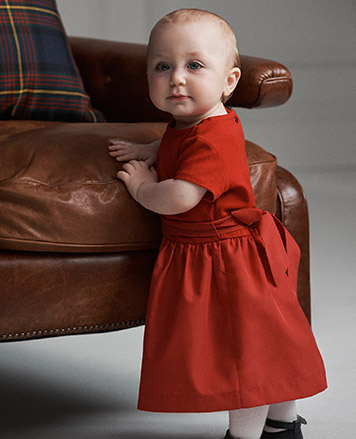 Baby girl wears red short-sleeve dress with sash.