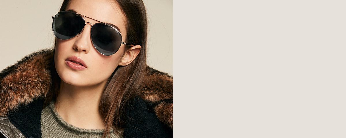 Model in dark mirrored pilot sunglasses & shearling-trim-collar jacket