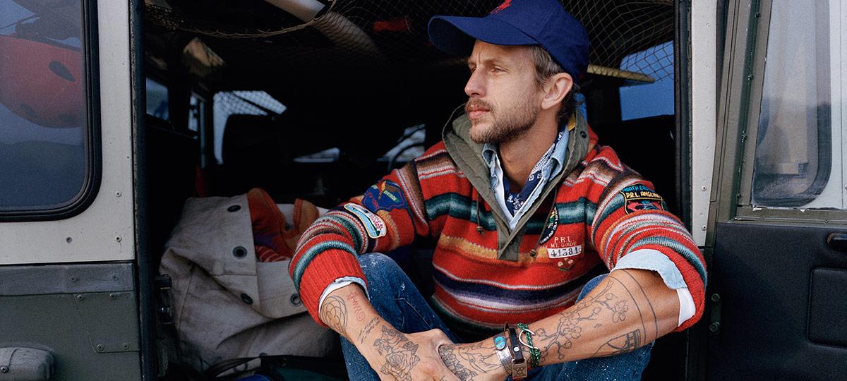 Man in multicolored striped hoodie sitting in back of van