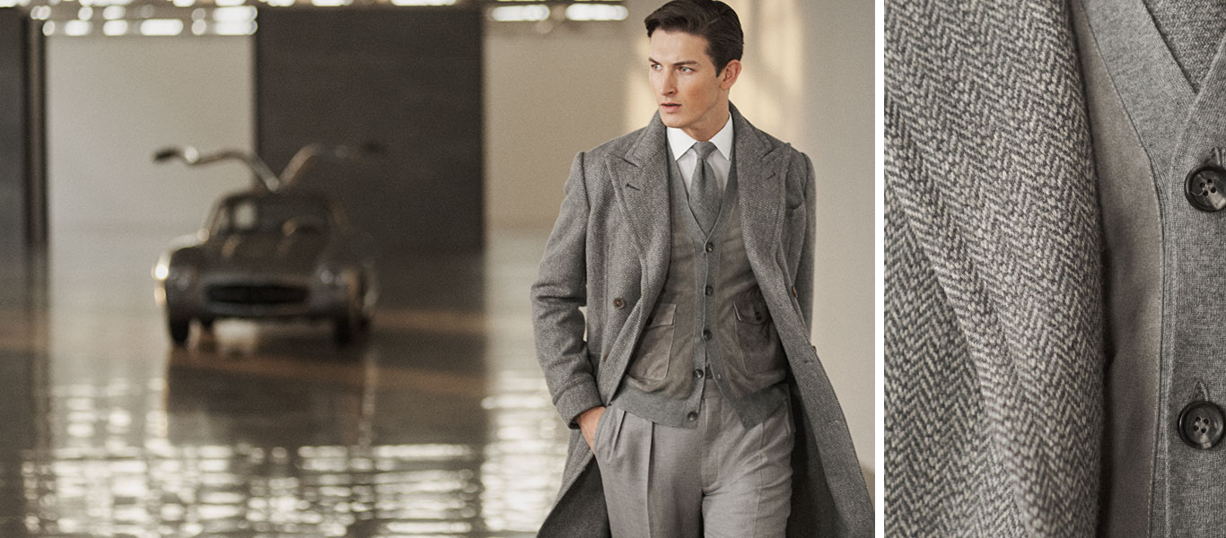 Man wears grey wool herringbone topcoat over grey outfit.