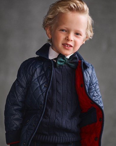 Boy wears navy quilted coat over navy cable-knit sweater