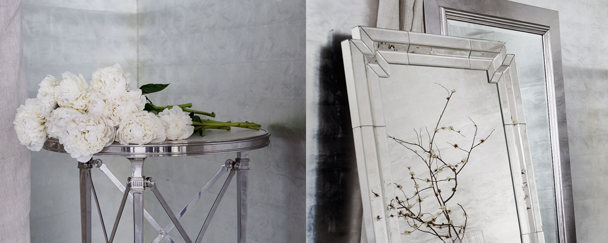 White flowers on metal end table next to mirrors