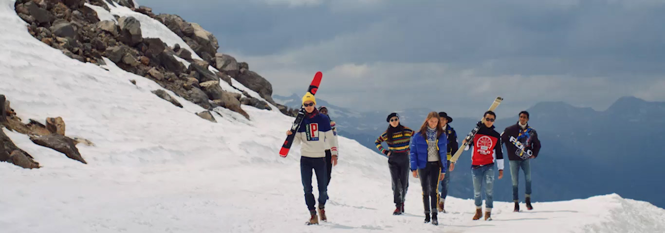 Men in color-blocked Polo outerwear carrying skis on mountain