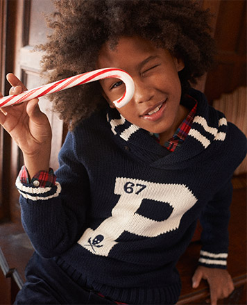 """Boy wears navy sweater with white """"P"""" at the front."""
