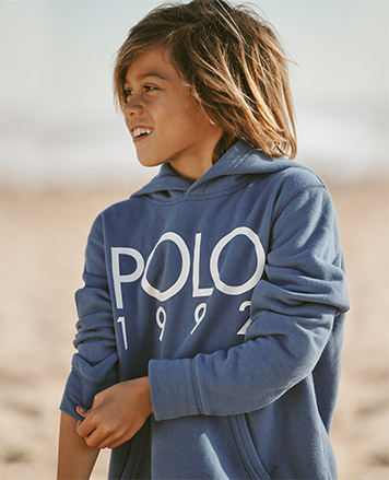 Boy wears blue hoodie with Polo 1992 at the front.