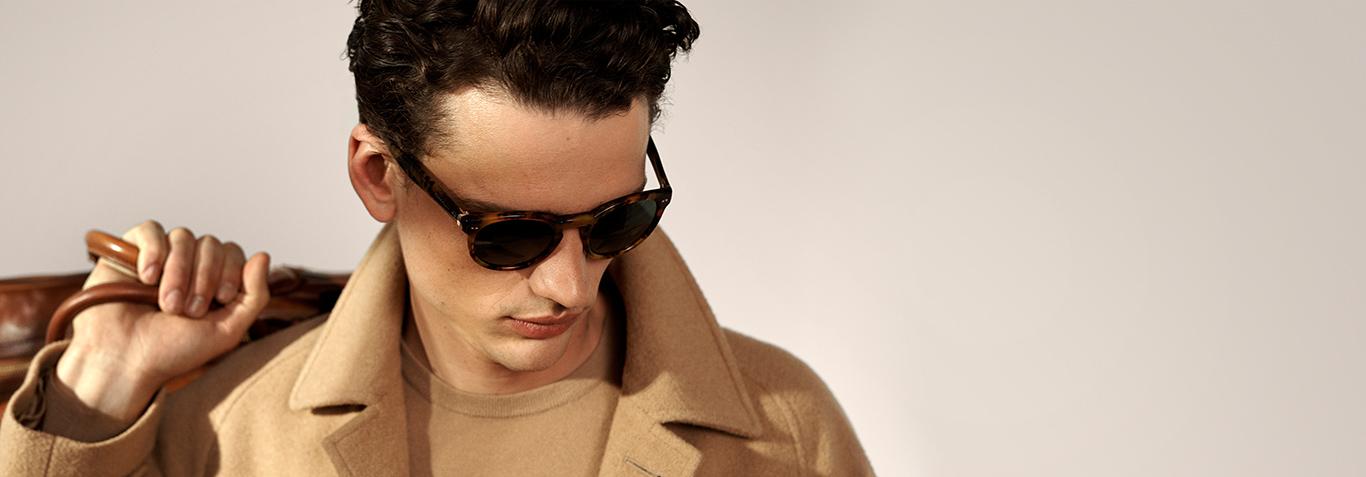 Man in tortoiseshell sunglasses with bag slung over shoulder