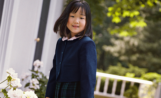 Girl wears navy buttoned jacket over plaid dress.
