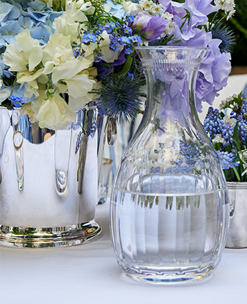 Crystal carafe on table next to flower arrangement
