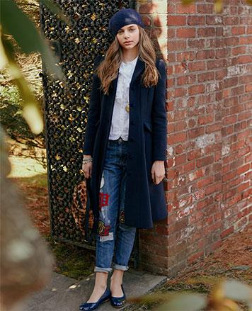 Girl wears long navy coat over jeans.