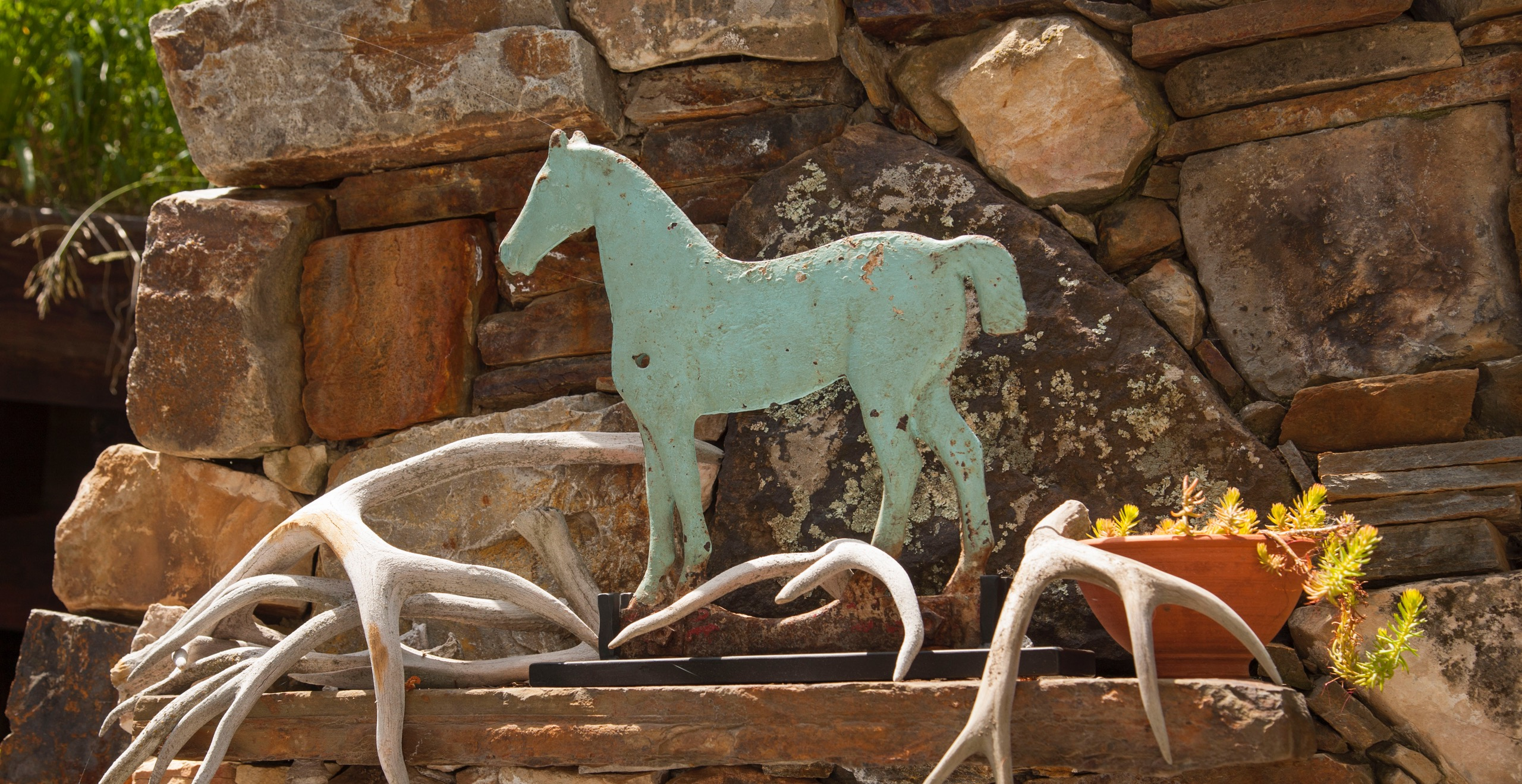 Buffy Birrittella's rustic Utah getaway is home to all kinds of horses—the one she rides and the ones she collects. Here, a blue horse windmill weight surrounded by antlers