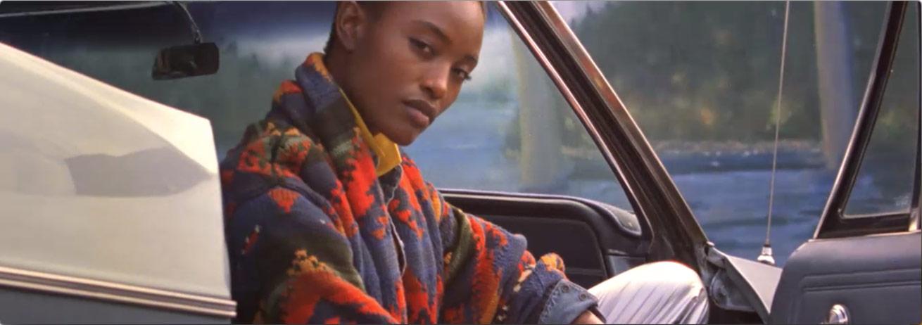 Woman in bright Southwestern-print shawl cardigan sits in car