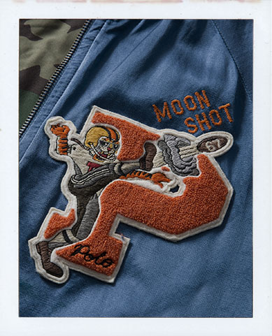 Man in blue baseball jacket with tiger football player patch